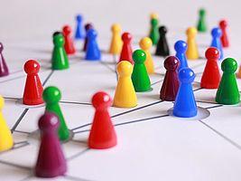 Image : des jetons de jeux, qui ressemblent à des petits bonhommes, de couleurs variées, sur sur un papier blanc, rejoints par des lignes.